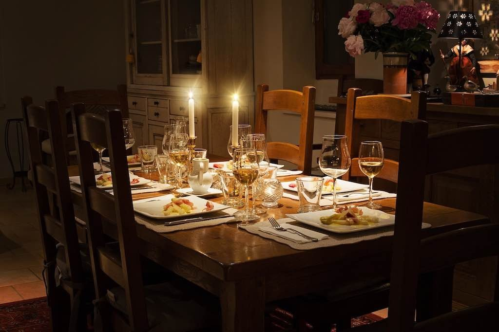 Dinner table set up with brown table candles and glasses and plates