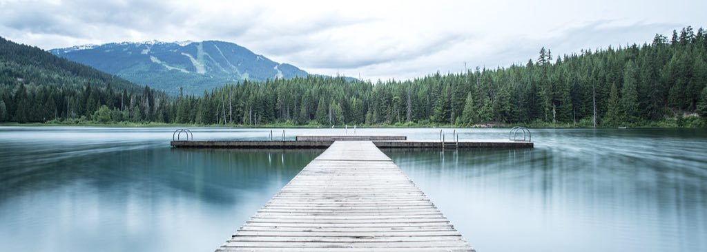 A pier on a lake surrounded by forest.