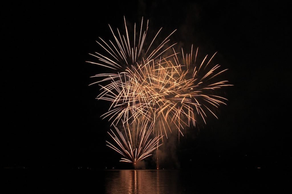 Fireworks shooting off over water.