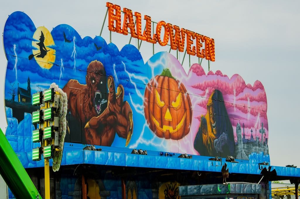Orange Halloween sign made out of lights at a fair.
