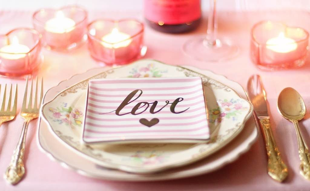 Dinner table set up with hearts and the word love.