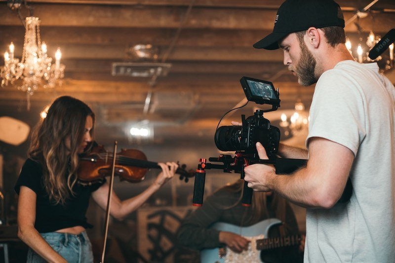 Man in hat holding a camera filming a girl with a violin for a music video
