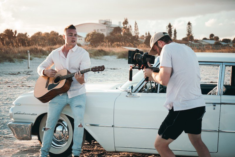 Man with dark hair playing a guitar on the beach being filmed but a man in a hat