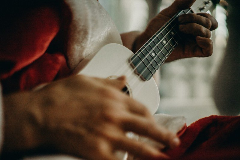 Person in Santa outfit playing the ukulele for a music video