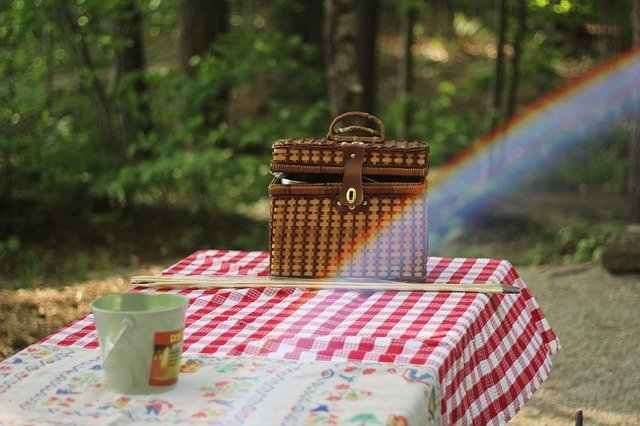 A picnic basket in a park on a table covered with a red and white table cloth.