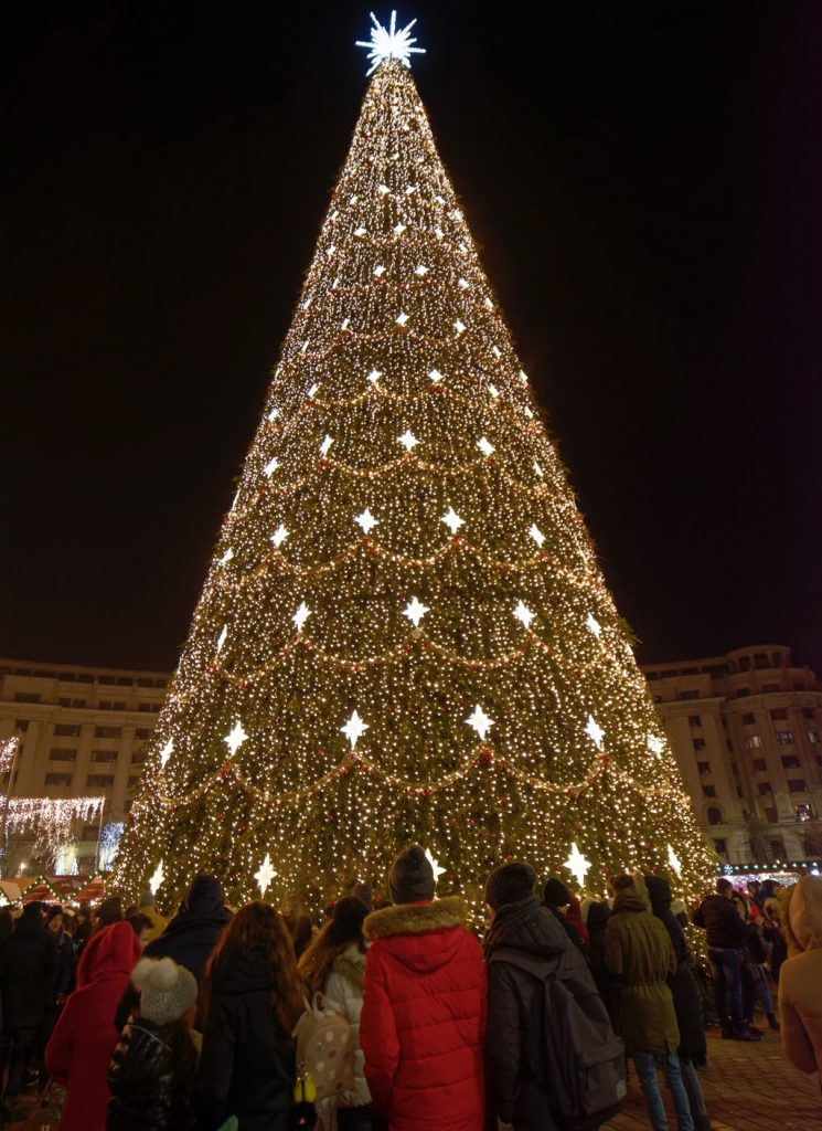 Huge Christmas tree in Romania with lots of people around it.