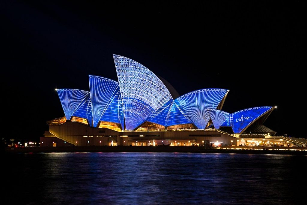 Famous opera house in Australia lit up with blue and white lights.
