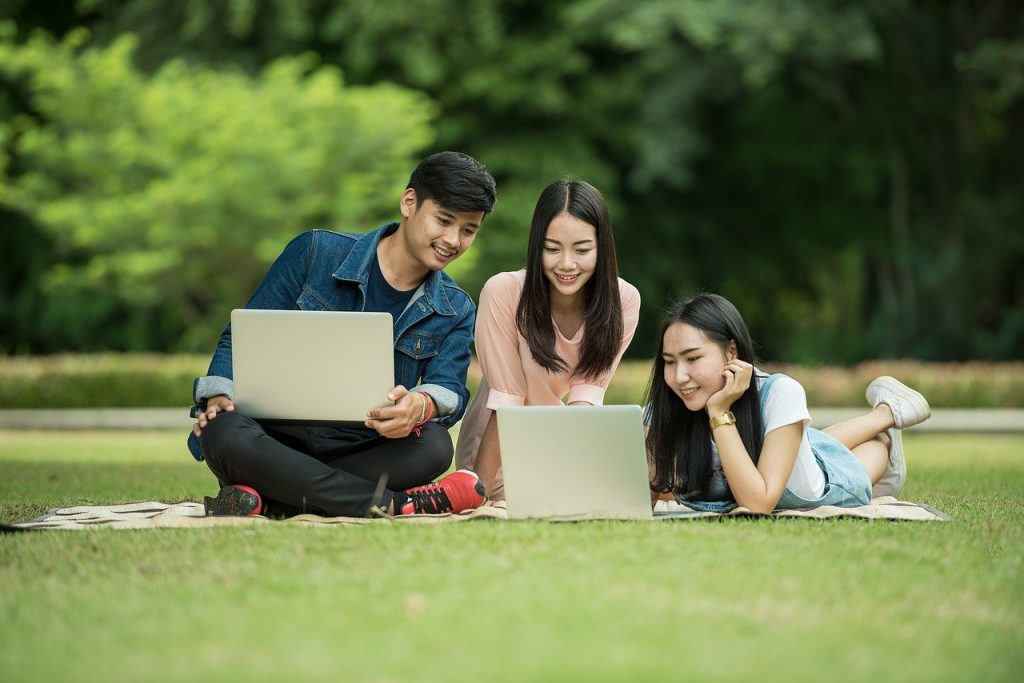A guy and two girls with a laptop watching a movie in a park.