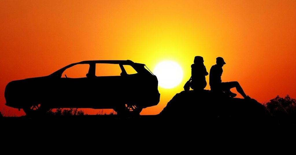 Silhouette of a couple sitting on a rock with a car that went for a drive at sunset.