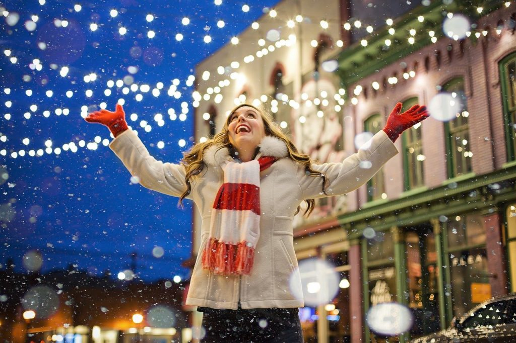 Happy blonde girl smiling in the show and looking at Christmas lights