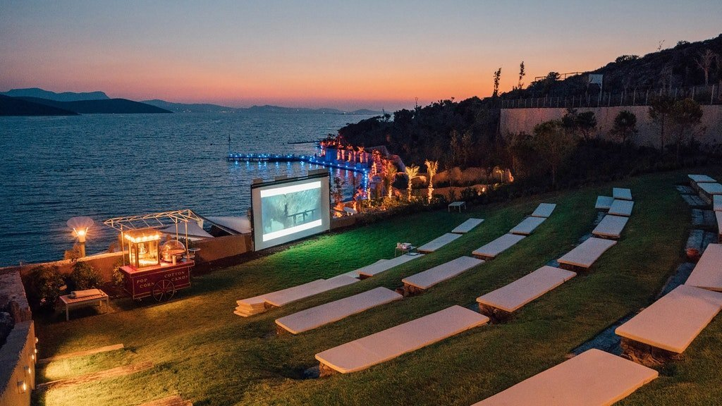 movie screen set up next to beach with popcorn stand