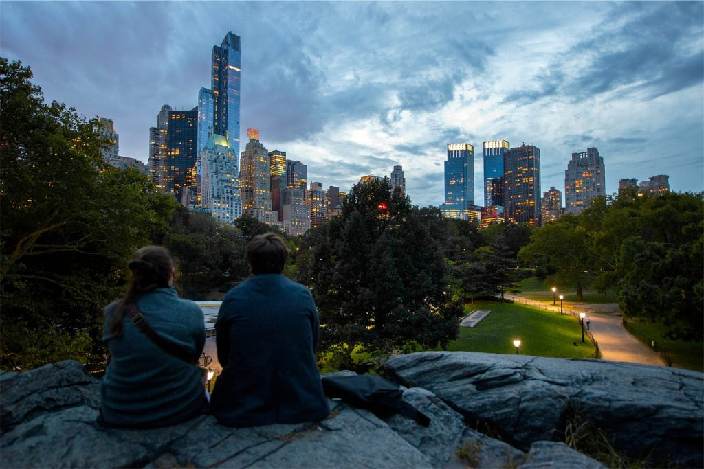Man and woman in a city park during sunset.