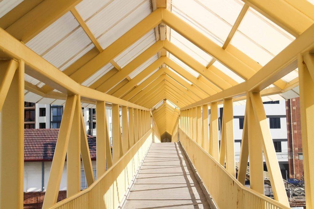 Yellow footbridge overpass extending to buildings