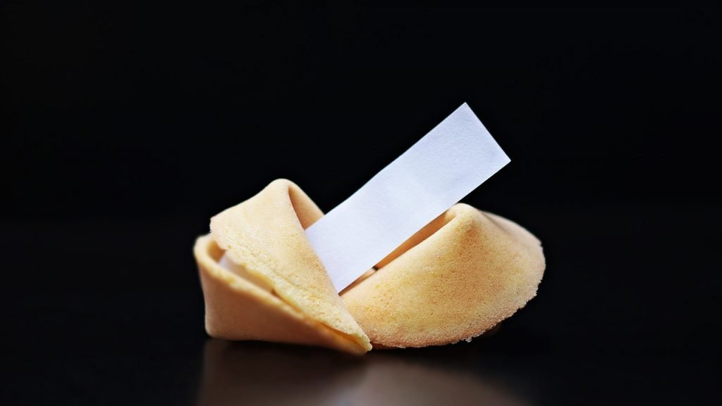 2 Fortune cookies with white note with black background.