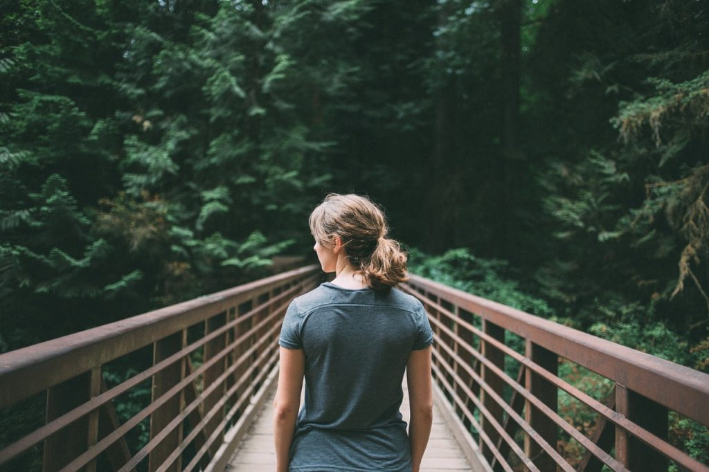 Girl with brown hair standing on a footbridge in the forest