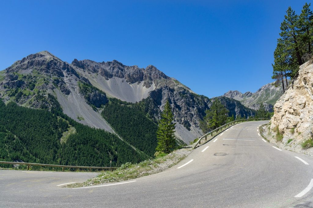 Alpine scenic road with lots of trees and blue sky