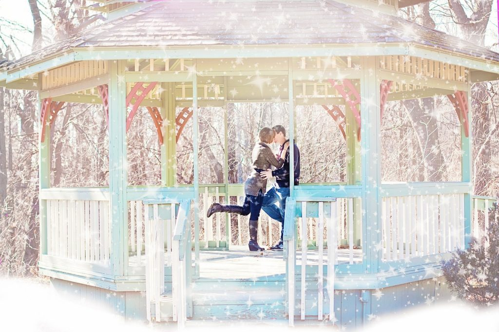 A girl and man kissing in a gazebo