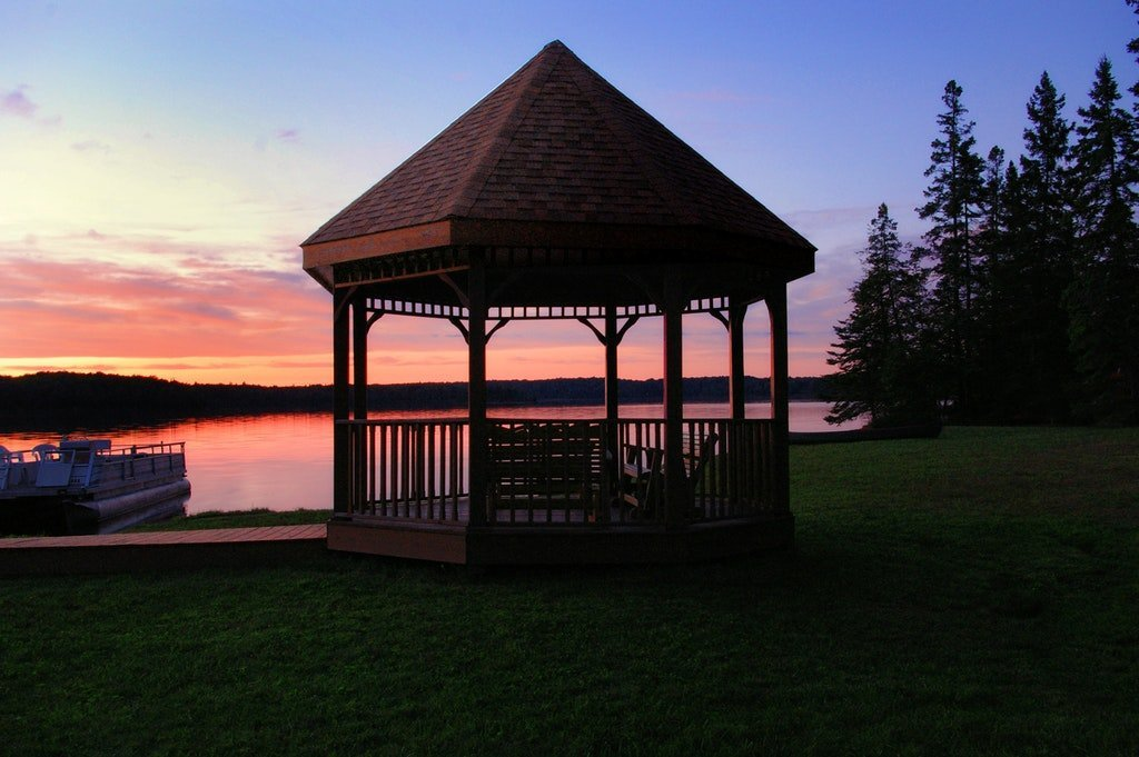 Wooden gazebo in the grass with a lake behind it.