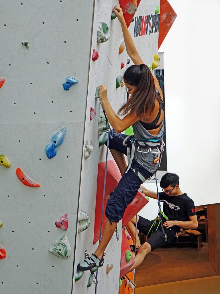 Girl and guy climbing at an indoor rock climbing gym