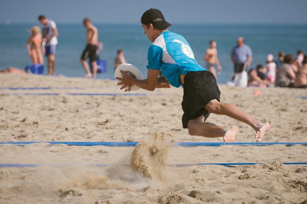 Guy with black hat playing ultimate frisbee in the sand