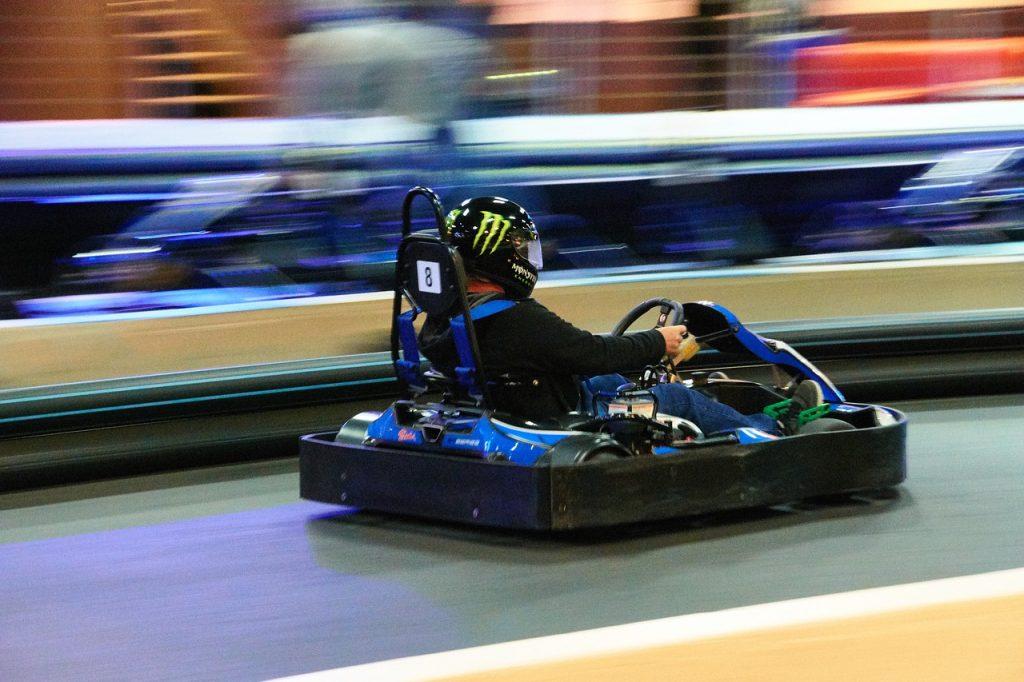 Guy with helmet on go kart racing