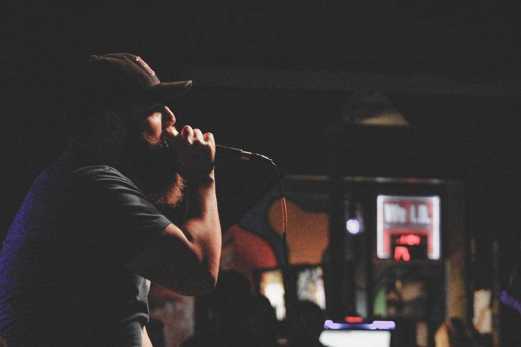 Man in hat holding microphone and singing karaoke