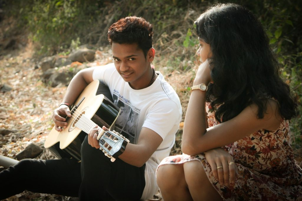 Young man playing guitar and singing to a girl