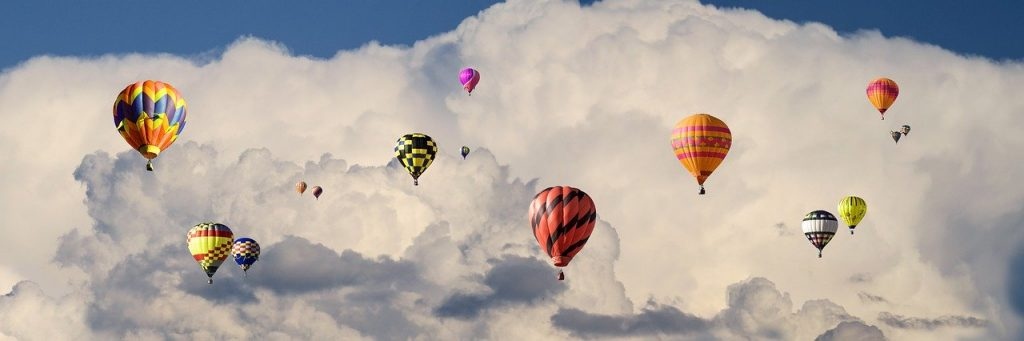 Several hot air balloons flying up in the clouds