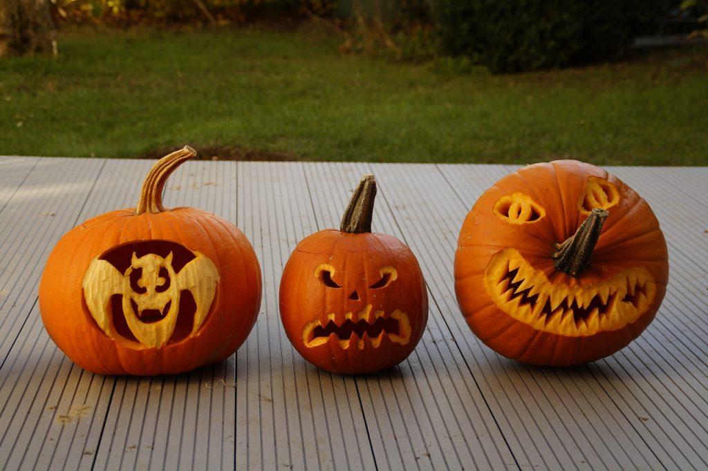 Three pumpkin carvings on a porch.
