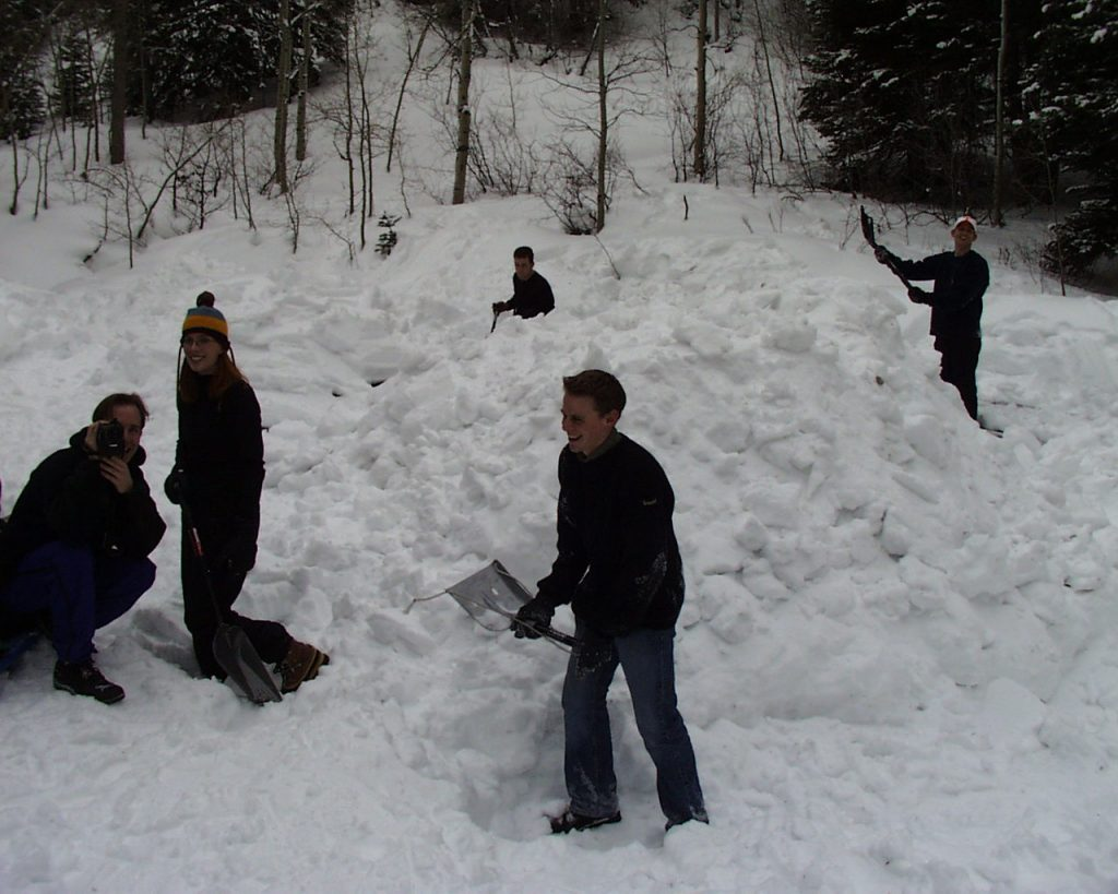 group of people in the forest making a snow cave