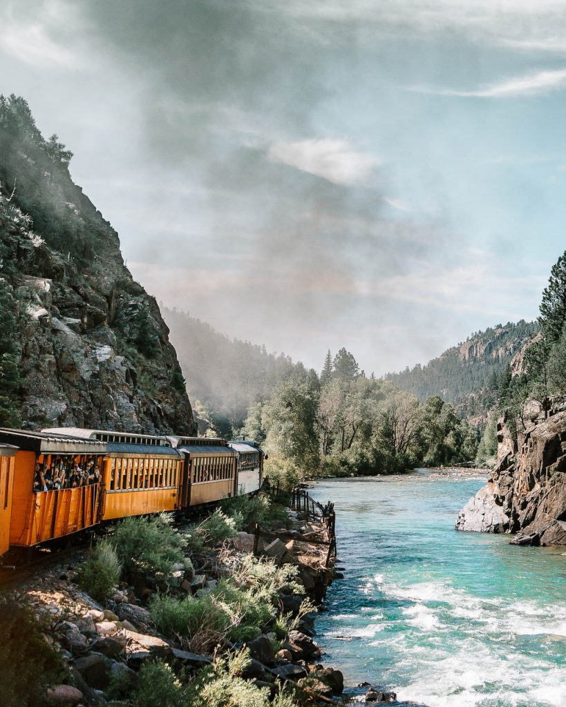 People aboard a scenic train ride along the mountains and stream.