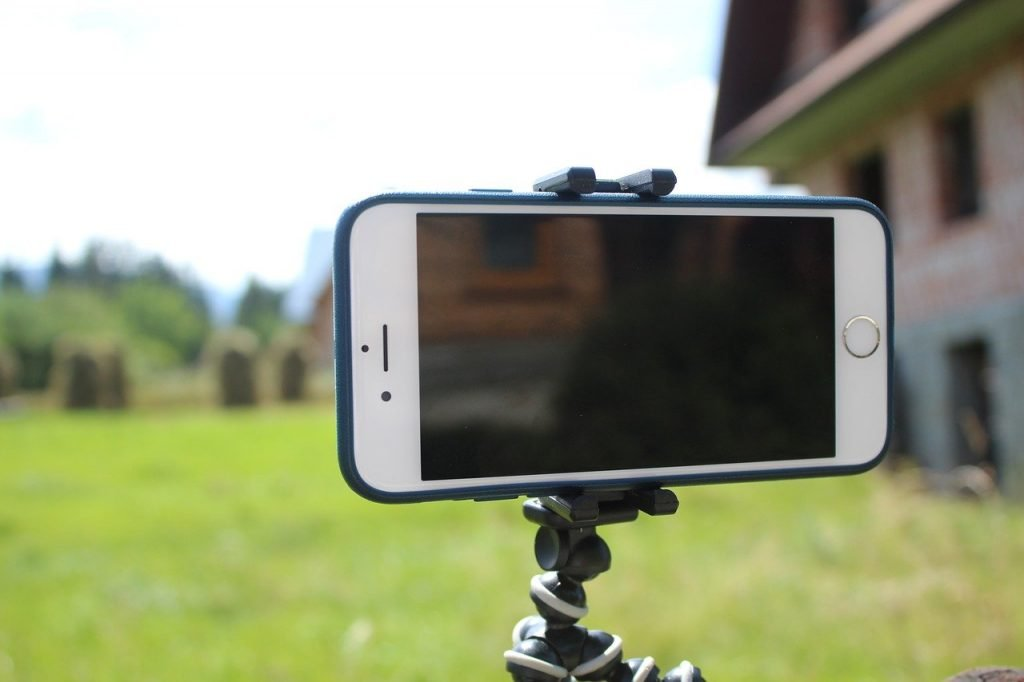 iPhone on a tripod in the grass next to a house