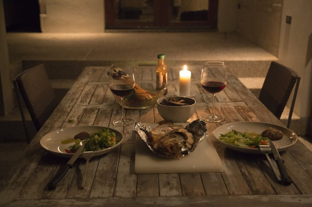 Romantic dinner on wooden table with fancy plates and silverware and wine glasses