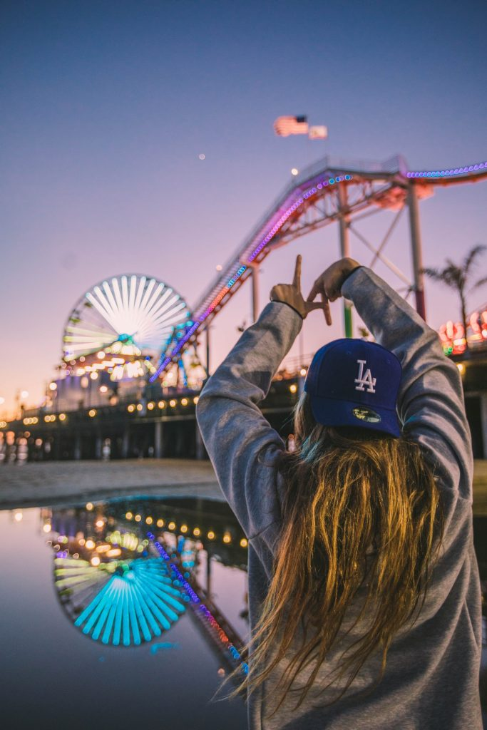 Girl with blue LA hat on in front of a theme park on the beach
