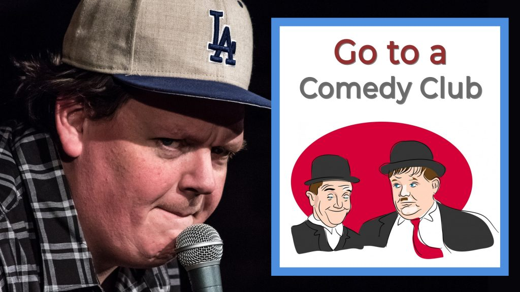 Go to a comedy club guy in hat talking in microphone