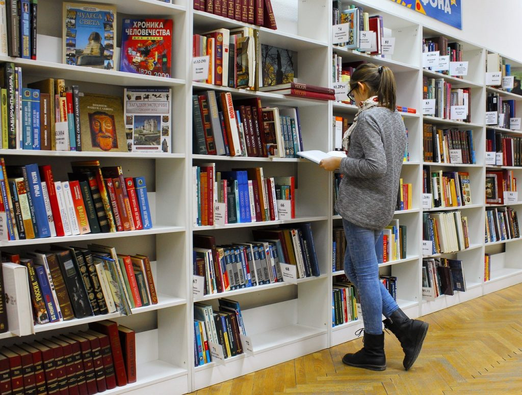 Girl with glasses and a pony tail reading a book at a bookstore or library