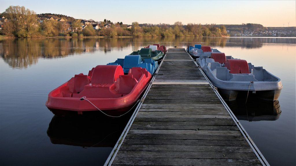 Several pedal boats on a lake at a dock