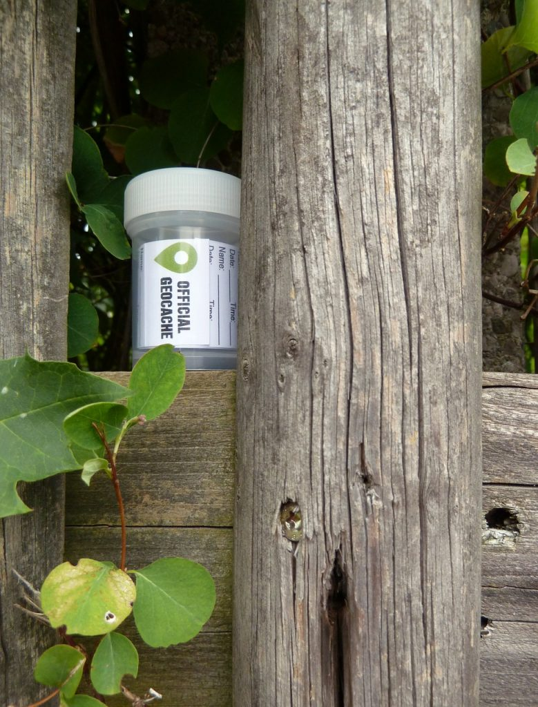 Official Geocaching geocache container on a wooden fence