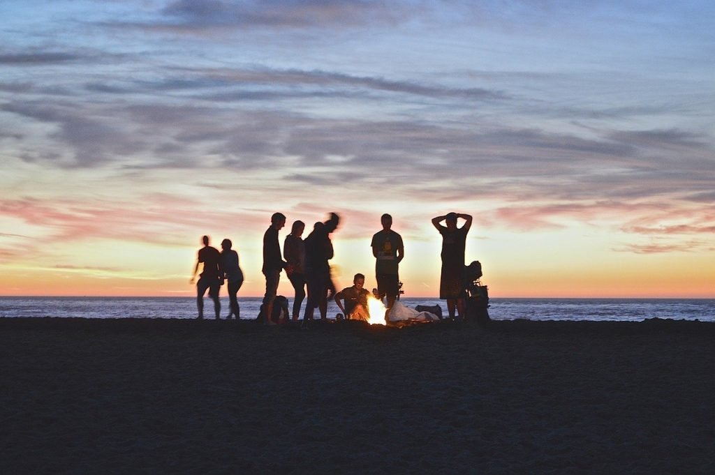 People on the beach next to a fire.