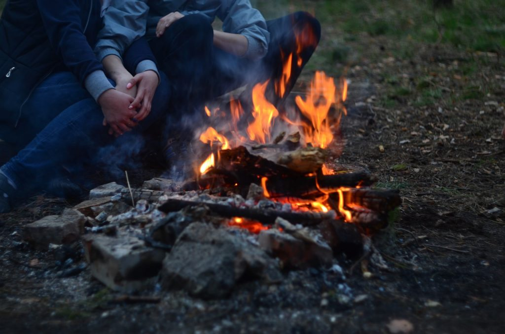 Couple holding hands next to a fire.