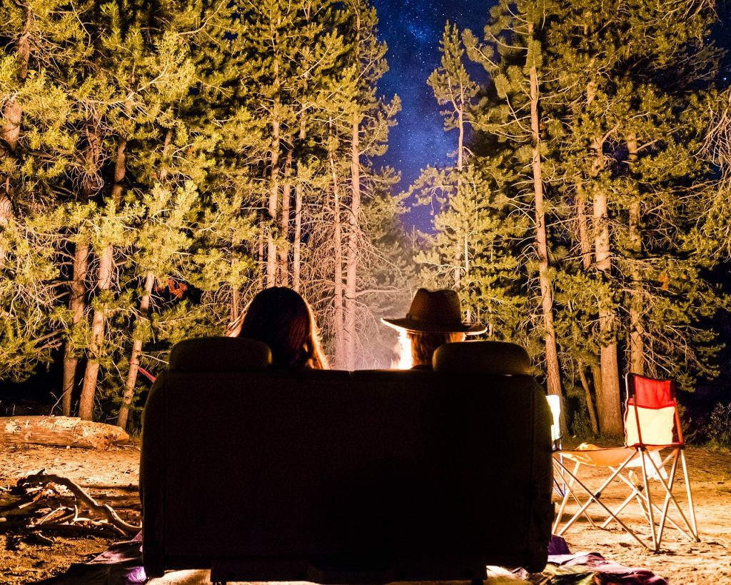 Couple sitting behind a fire on a romantic date.