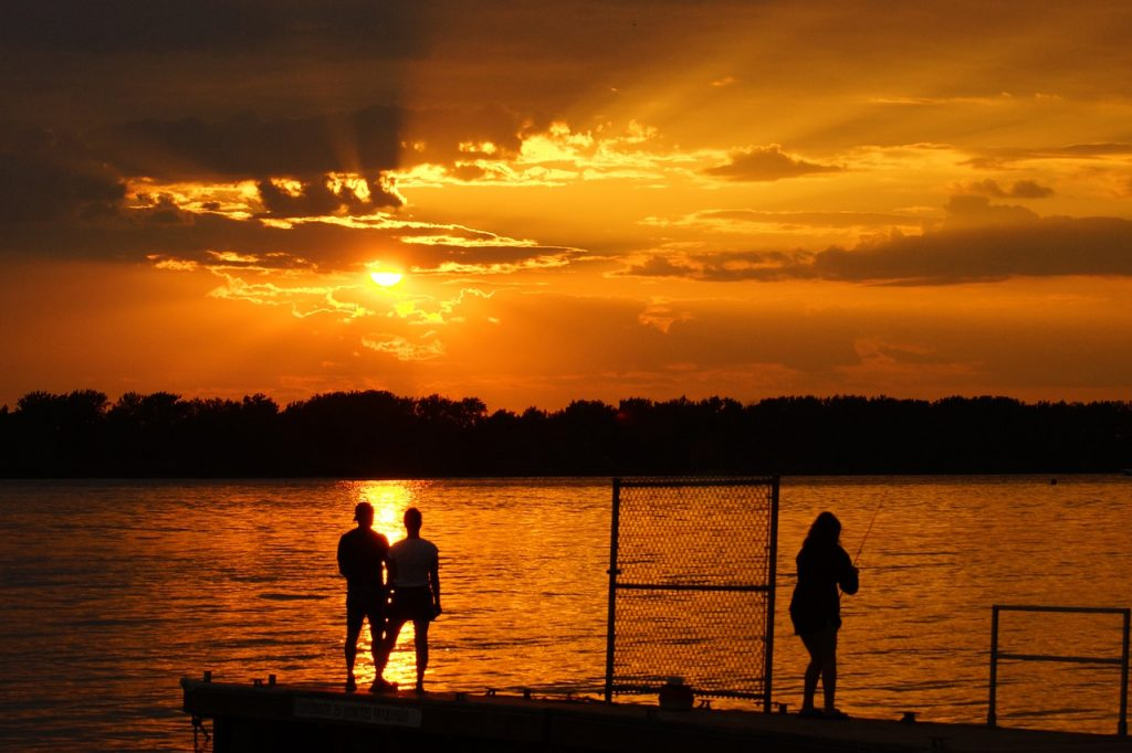 Sunset on a lake with people fishing while on an adventure date.