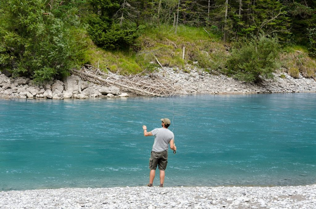 Man fly fishing on a blue river.