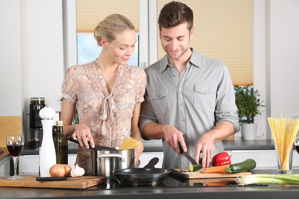 Couple on a group date cooking together.