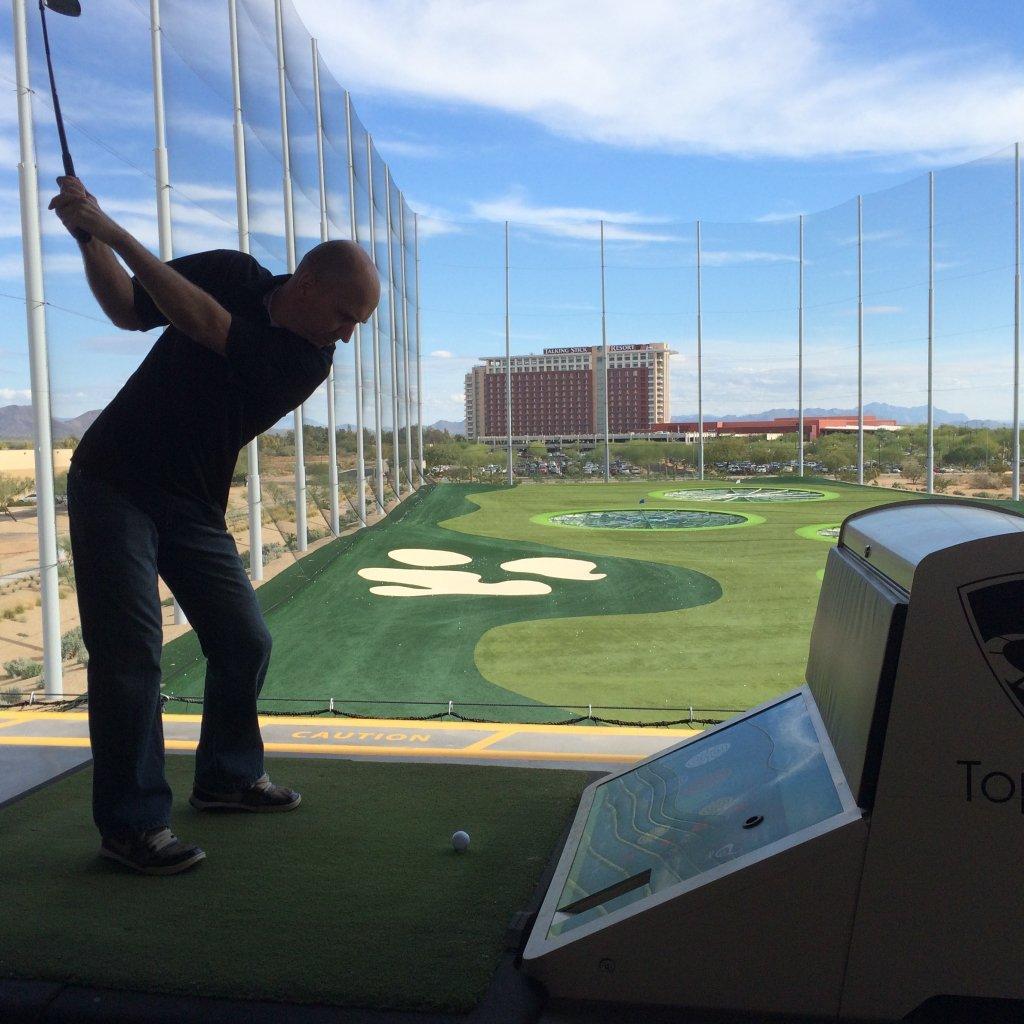 Guy swinging a golf club at TopGolf.