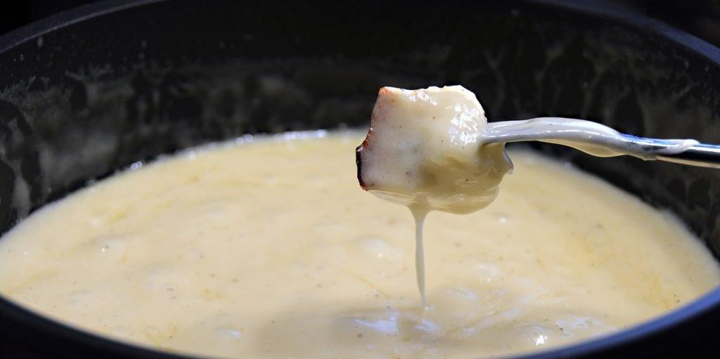 Cheese fondue in a pot.