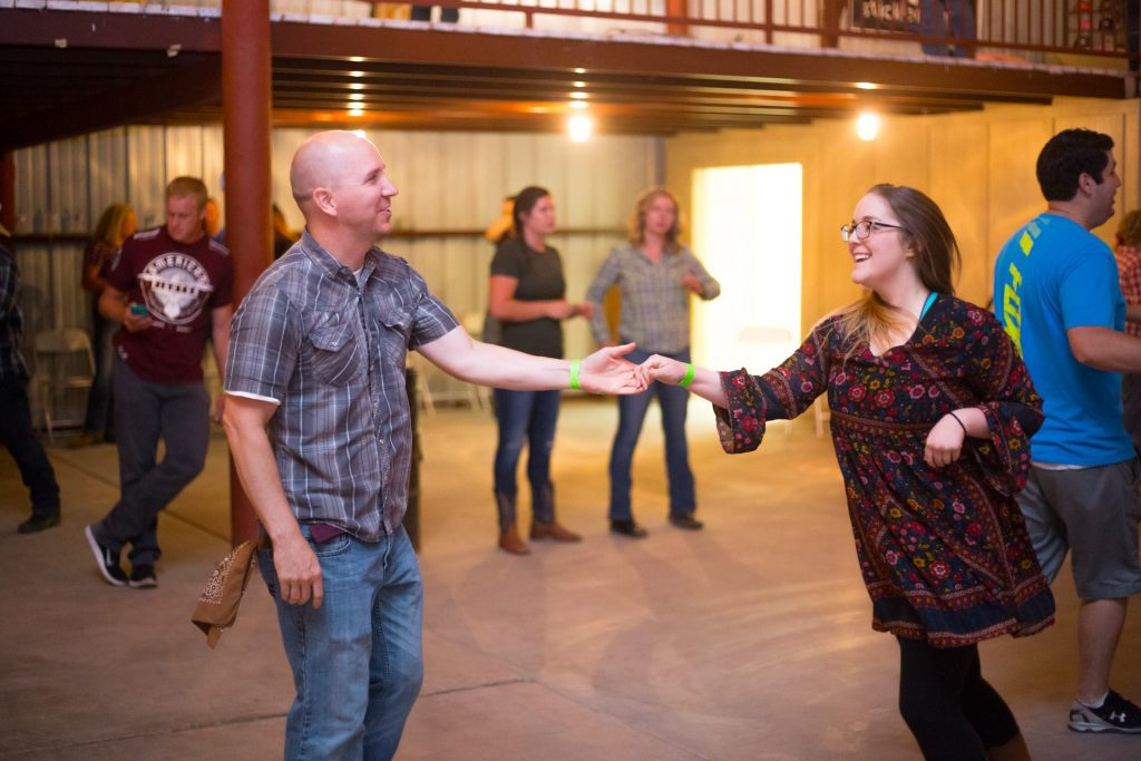 Guy with girl country dancing in a barn