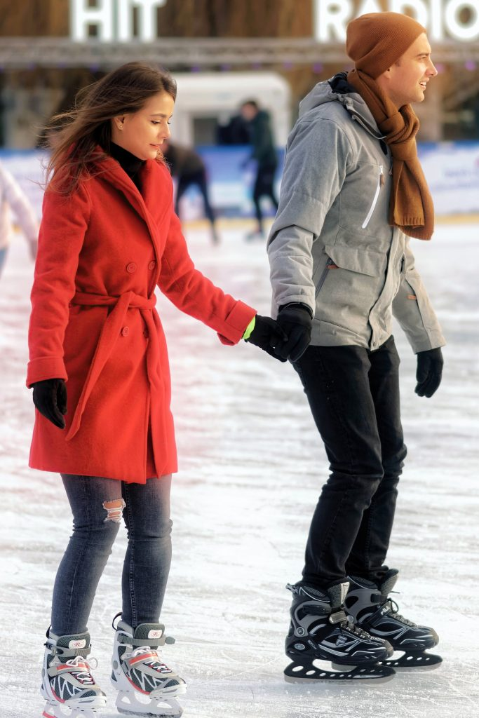 Couple holding hands on the ice skating rink.