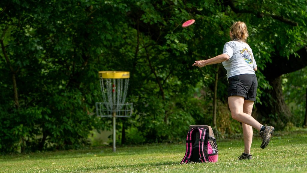 Girl playing disc golf at a park