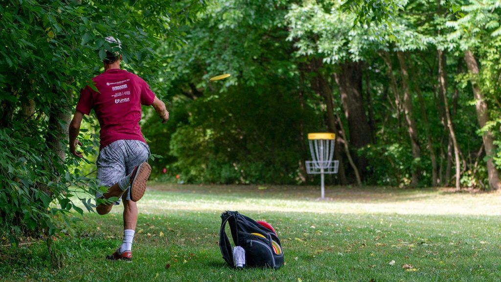 Man playing frisbee golf at a park.